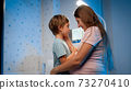Portrait of young pregnant mother stroking and soothing her scared little son at night 73270410