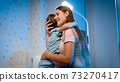 Beautiful young mother talking to her little toddler boy being scared of nightmare at night. Parent soothing and caressing child 73270417