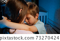 Portrait of little upset and sad toddler boy hugging and kissing his mother before going to sleep at night. Loving and caring parents and children 73270424
