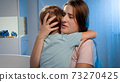 Portrait of young loving mother soothing and caressing scared little boy in children room at night. CHild being scared and crying of nightmare or bad dream 73270425