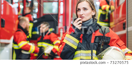 Beautiful fire fighter woman with her helmet standing in the firehouse 73270575