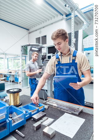 Worker looking for small parts to continue manufacturing stuff in factory 73270700