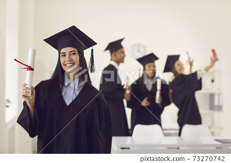 Female graduate shows the camera a diploma in her hands while standing in the classroom. 73270742