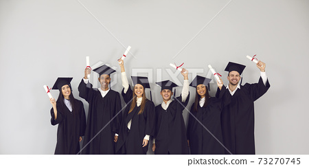 Group of happy multiethnic college or university graduates holding up their diplomas 73270745
