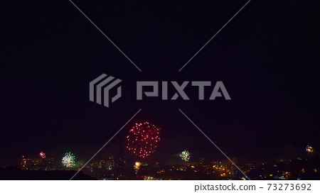 many flashes of fireworks over the night city. general holiday 73273692