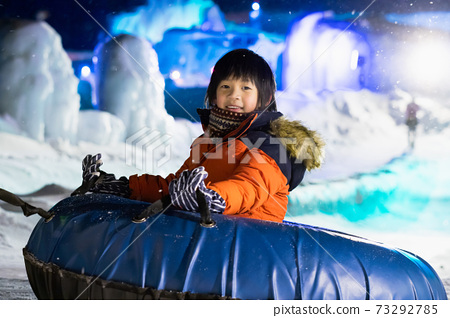 Asian child playing sledge in snow festival 73292785