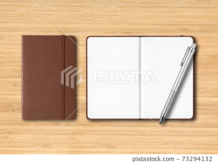 Leather closed and open lined notebooks with a pen on wooden background 73294132