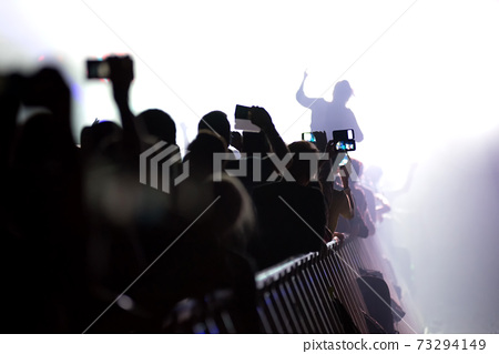 Concert crowd with raised arms holding smartphones at concert 73294149