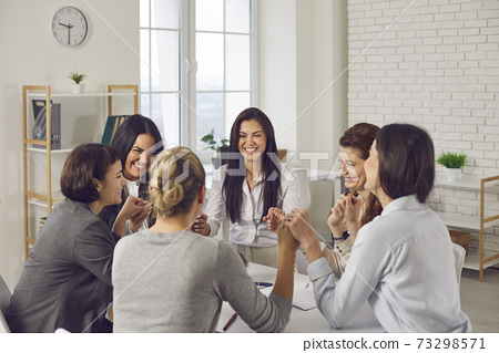 Team of happy young business women sitting around office table and holding hands 73298571