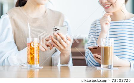 一個年輕的女人,看著在一家咖啡館的智能手機 73305729