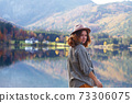 girl stands on the shore of a mountain lake 73306075