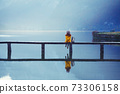 tourist girl in a hat and with a backpack stands on a wooden bridge 73306158
