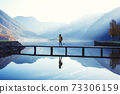 tourist girl in a hat and with a backpack stands on a wooden bridge 73306159