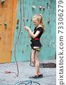 little girl climbing up the wall 73306279