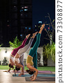 Asian weman group do yoga in city at night 73308877