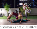 Asian weman group do yoga in city at night 73308879