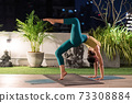 Asian woman do yoga in city at night 73308884