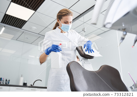 Dentist sterilize the medical equipment inside a dental clinic 73312821