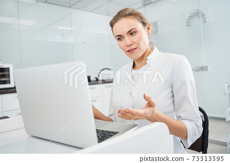 Blonde doctor talking with colleagues through a video call 73313595