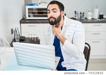 Doctor gesturing and showing something while consulting patient 73313635