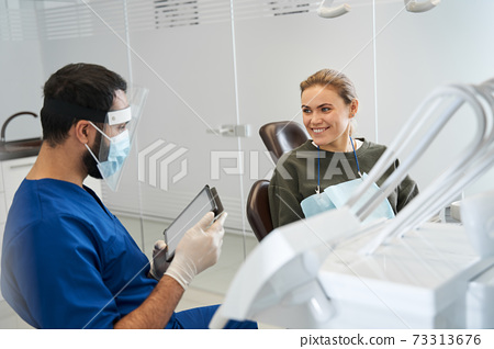 Male dentist talking to his woman patient in dentist surgery 73313676