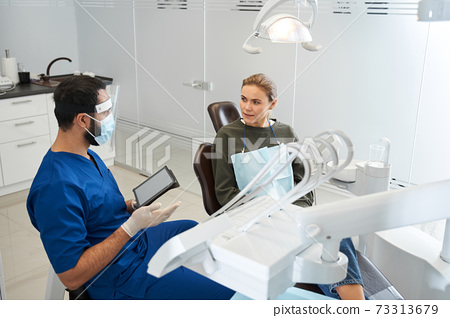 Patient and dentist are discussing teeth image on digital tablet 73313679