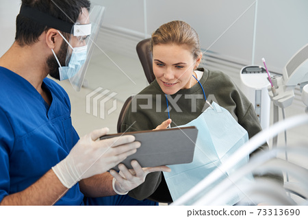 Patient and dentist are looking at teeth image on digital tablet 73313690