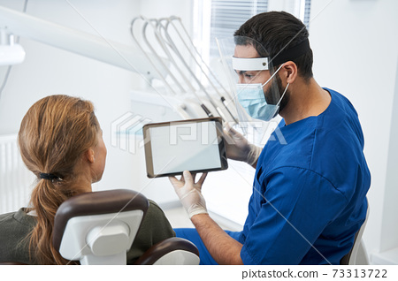 Male dentist talking to his woman patient in dentist surgery 73313722