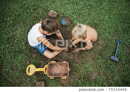Top view of two brothers sitting on  grass playing with mud 73314449