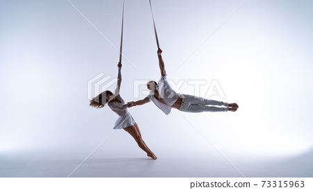 Aerial straps duo wearing white costume on white background doing performance. Concept of desire, attraction and relationship 73315963