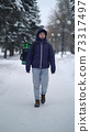 Courier is delivering food with backpack at winter 73317497