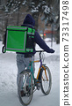 Courier is delivering food with backpack at winter 73317498