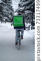 Courier is delivering food with backpack at winter 73317499