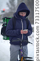 delivery man with green bagpack awaiting the order for delivery 73317500