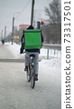 Courier is delivering food with backpack at winter 73317501