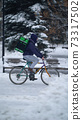 Courier is delivering food with backpack at winter 73317502