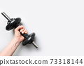 Female hand with black dumbbell on grey background. Sport fitness equipment. 73318144