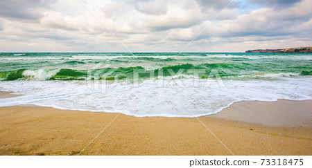 sea tide on a cloudy sunset. green waves crashing golden sandy beach. storm weather approaching. summer holiday concept 73318475