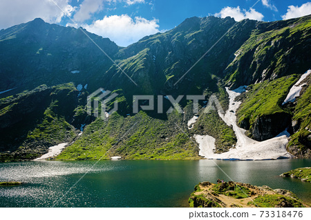 balea lake in fagaras mountain of romania. beautiful landscape in summertime. rocky slopes with grass in snow. sunny weather with fluffy clouds on the sky. popular travel destination 73318476