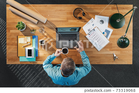Top view of businessman working on computer at desk with paperwork in home office. 73319068