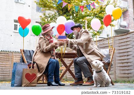 Happy senior partners in outdoor cafe in city, couple celebrating birthday. Coronavirus concept. 73319182