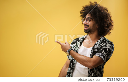 Portrait of mature man in a studio on yellow background, pointing fingers to copy space. 73319200