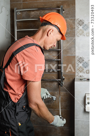 The worker is installing a heating element in the towel warmer. 73320493