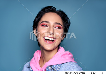 Happy teen girl face with dental healthy smile isolated on blue background 73321604