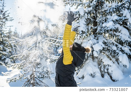 Young woman throwing snow in the air at sunny winter day. 73321807