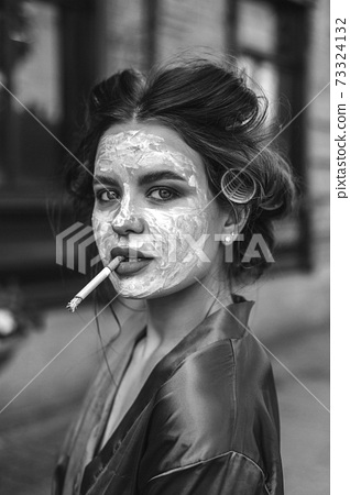 Girl in home clothes walking, wearing a mask, and with milk 73324132