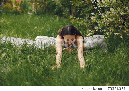 Woman practicing advanced yoga in a park 73328381