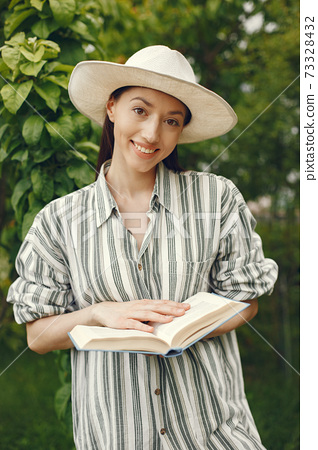 Woman in a hat with a book in a garden 73328432