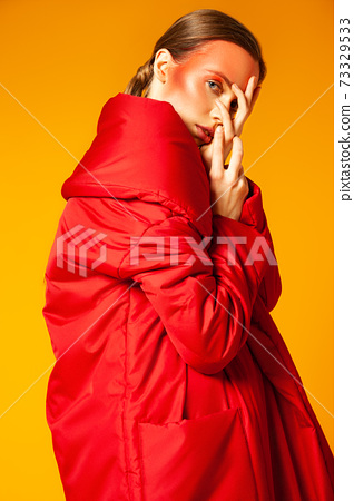 Woman in trendy coat touching face against yellow background 73329533