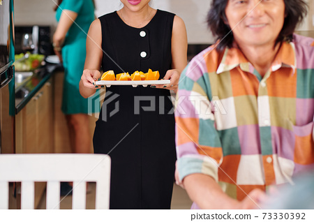 Woman bringing orange slices to table 73330392